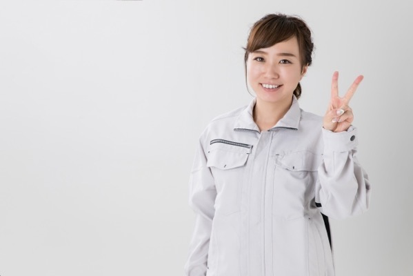 2の指をする作業着の女性