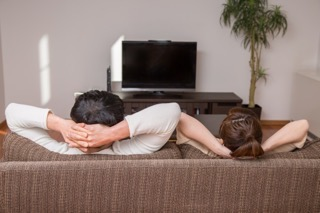 テレビの前のソファーでくつろぐ男女